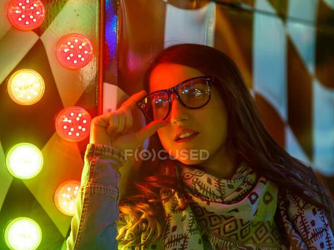 Впевнена жінка в мішках і сонцезахисних окулярах біля стіни з неоновими вогнями на вулиці вночі — стокове фото