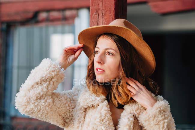 Positivo attraente giovane donna in caldo usura e cappello guardando altrove — Foto stock