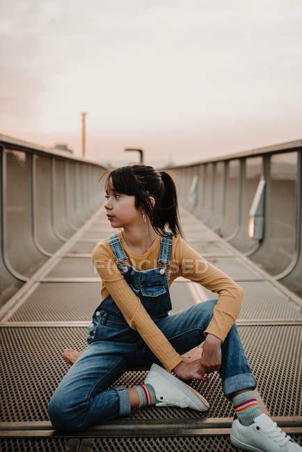 Ragazza seduta su skateboard su Ponte di metallo e guardando lontano — Foto stock