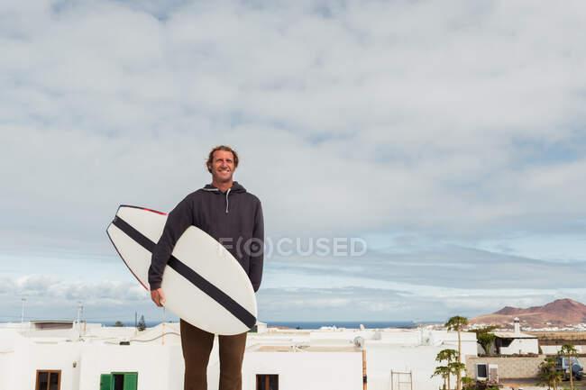 Sonriente hombre de pie con tabla de surf - foto de stock