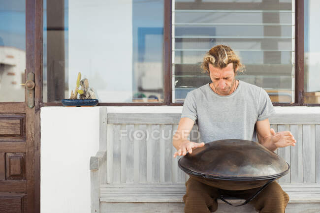 Uomo biondo seduto sulla panchina con grande tamburo a mano — Foto stock