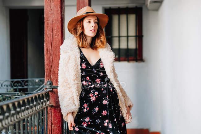 Positif attrayant jeune femme dans l'usure chaude et chapeau regardant loin et debout près de la maison et la clôture — Photo de stock