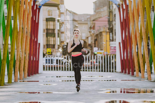 Женщина в спортивной одежде с наушниками и смартфоном работает на улице — стоковое фото