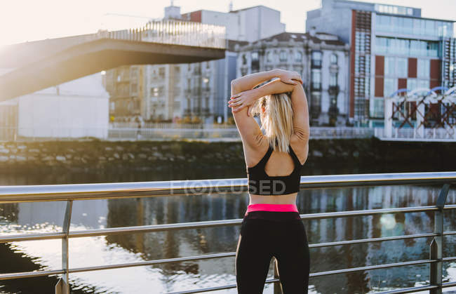Back view of woman in sportswear stretching hands on quay near water in city in sunny day — Stock Photo