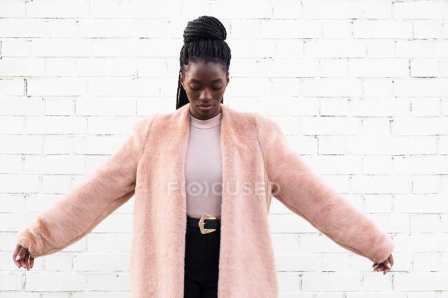Attraktive schlanke trendige Afroamerikanerin mit offenen Armen, die auf weißen Backsteinhintergrund herabblickt — Stockfoto