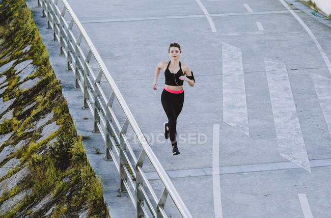 From above of woman in sportswear running on quay near water in city — Stock Photo