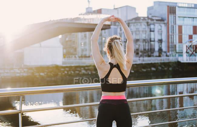 У сонячному дні жінка в спортивному лаві простягає руки на набережній біля води. — стокове фото