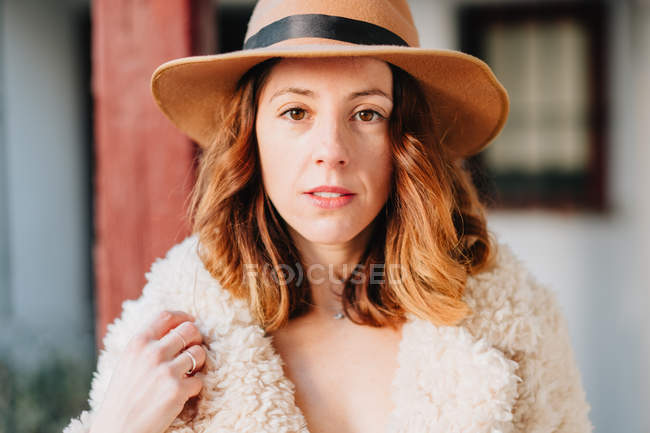 Positive attractive young woman in warm wear and hat looking at camera — Stock Photo