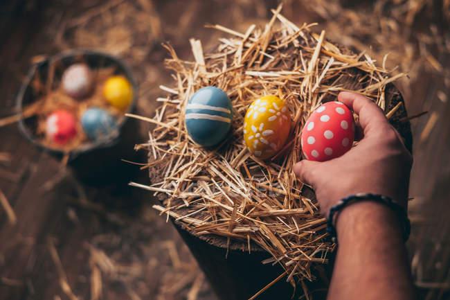 Mão da pessoa que prende o ovo decorativo sobre o coto de madeira no fundo rústico — Fotografia de Stock