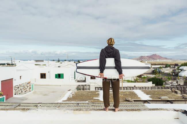 Вид сзади на молодого парня в свитере, стоящего с доской для серфинга на крыше и смотрящего на дома и каменный холм — стоковое фото