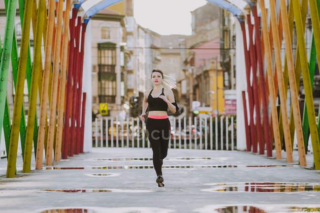 Mujer en ropa deportiva con auriculares y smartphone corriendo en la calle - foto de stock