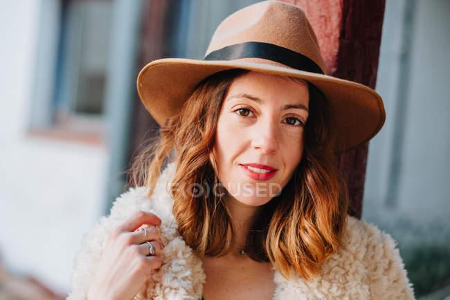 Positive attraktive junge Frau in warmer Kleidung und Hut blickt in die Kamera — Stockfoto