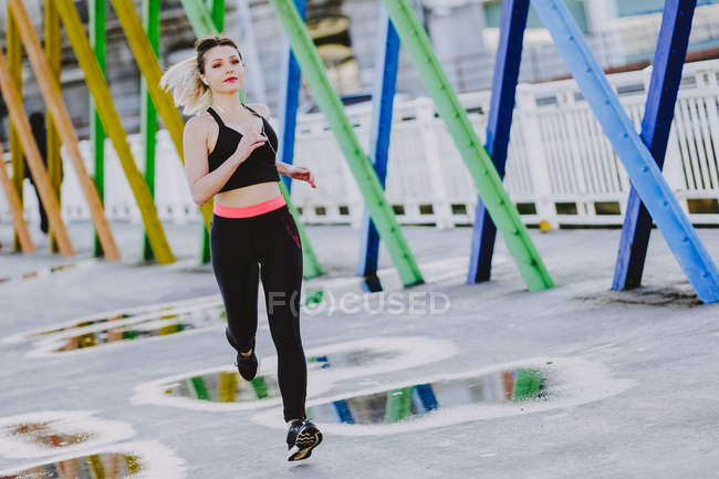 Woman in sportswear with earphones and smartphone running on street — Stock Photo