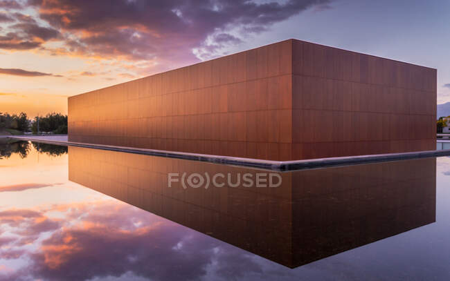 Glade of water in pool around modern abstract construction with brown walls in evening — Stock Photo
