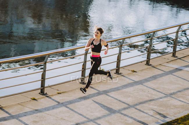 Femme en vêtements de sport courant sur le quai près de l'eau en ville — Photo de stock