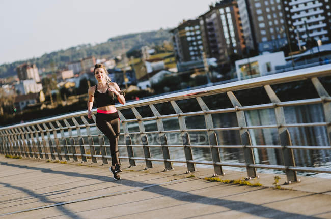 Mujer en ropa deportiva corriendo en muelle cerca del agua en la ciudad - foto de stock