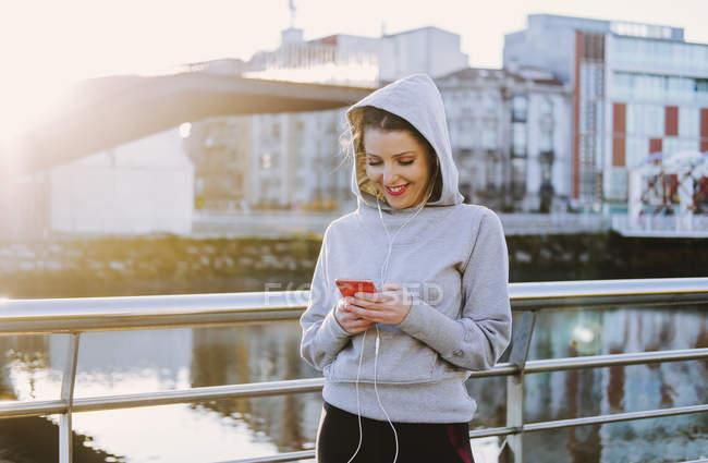 Женщина в спортивной одежде и толстовке с наушниками возле набережной — стоковое фото