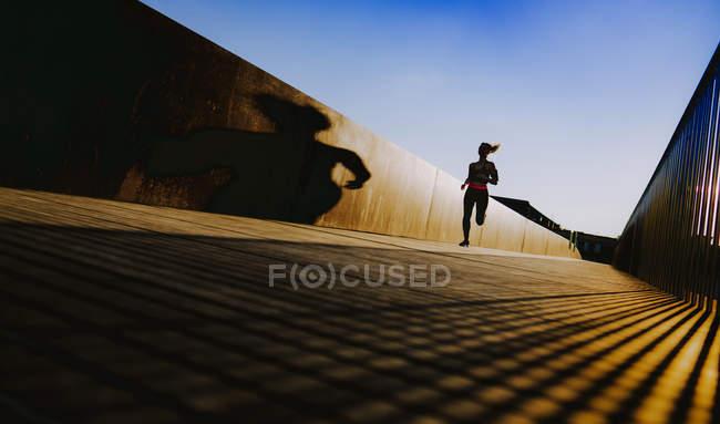 Женщина в спортивной одежде бежит по тропинке в солнечную погоду с голубым небом — стоковое фото