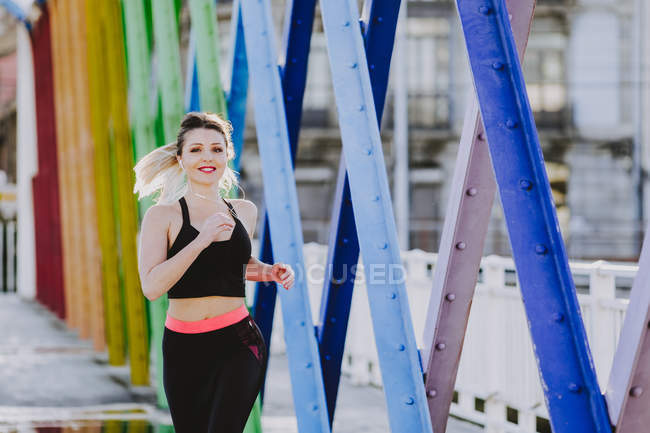 Woman in sportswear with earphones and smartphone running on street — Photo de stock