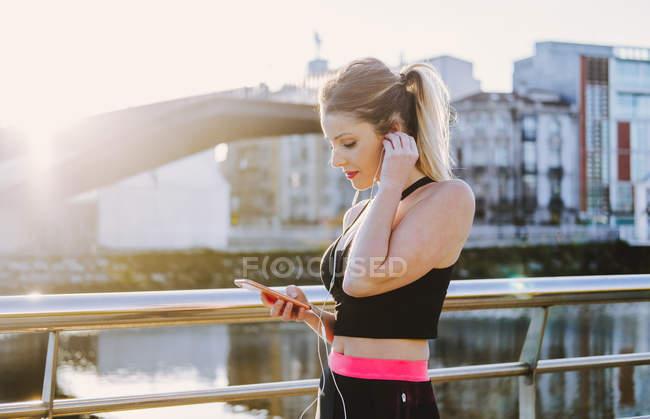 Femme en vêtements de sport avec écouteurs naviguant sur le téléphone mobile près de l'eau sur le remblai — Photo de stock