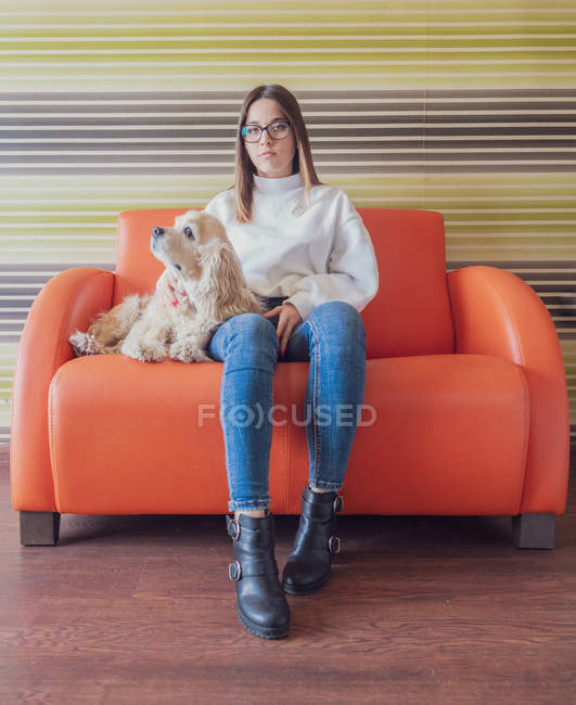 Proud stylish teen in eyeglasses sitting on armchair with dog and looking at camera in room — стокове фото