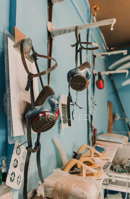 Respiradores colgando cerca de los planos de carpintería y otras herramientas en el lugar de trabajo - foto de stock