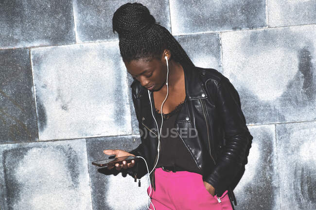 Attractive slim trendy African American woman in earphones listening music on mobile phone on grunge brick background — Stock Photo