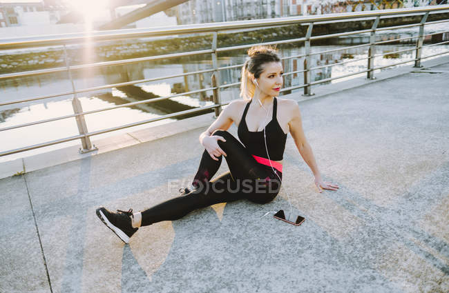 Woman in sportswear with earphones and mobile phone stretching legs near water on embankment — Photo de stock