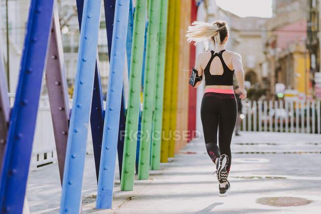 На тлі спортивного одягу жінка з навушниками та смартфонами біжить по вулиці. — стокове фото