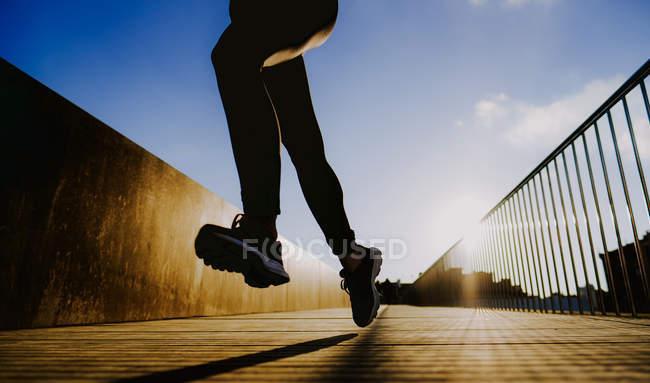 Обрезанный образ женщины в спортивной одежде, бегущей по улице в солнечную погоду — стоковое фото