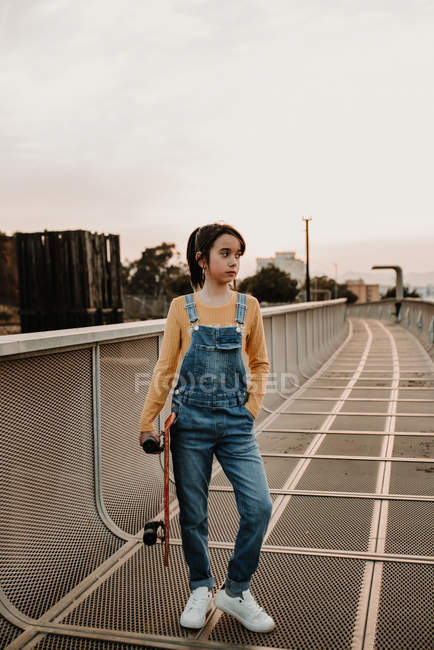 Stylish teen girl in jean overall with hand in pocket holding skateboard on metal bridge in city — Stock Photo