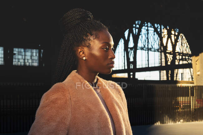 Attractive slim trendy African American woman looking away and standing near construction — Stock Photo