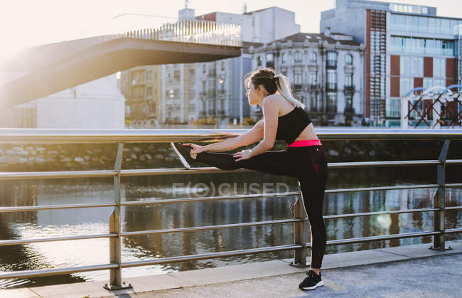 Mulher em sportswear esticando as pernas no cais perto da água na cidade em dia ensolarado — Fotografia de Stock