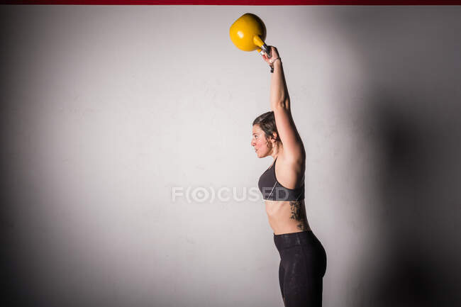 Athletic young concentrated woman in sportswear upping kettlebell in gym — Stock Photo