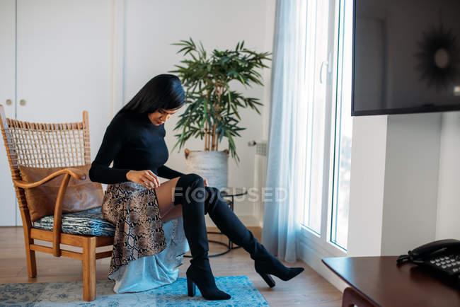 Стилист красивая молодая черная женщина, сидящая в современном кресле — стоковое фото