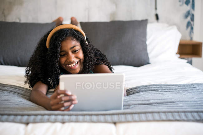 Black teenage girl with curly hair smiling looking at camera and using tablet and headphones on bed — Stock Photo