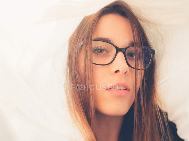 Teen in eyeglasses looking at camera between white material — Stock Photo