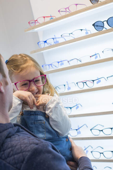 Cute young girl trying on glasses in an eyewear store — Stock Photo