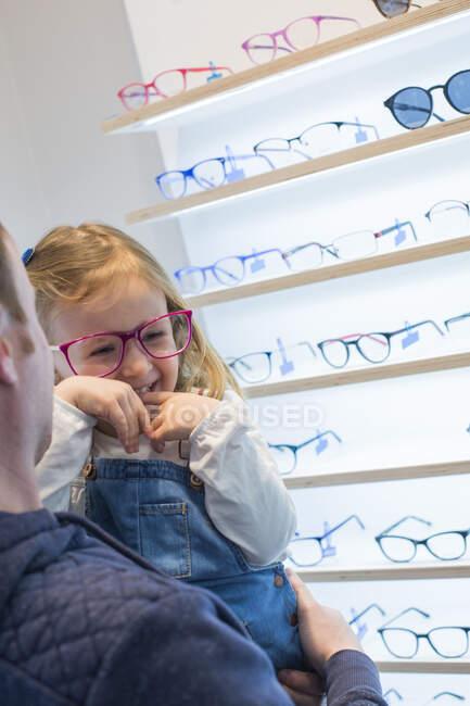 Милая молодая девушка примеряет очки в магазине очков — стоковое фото