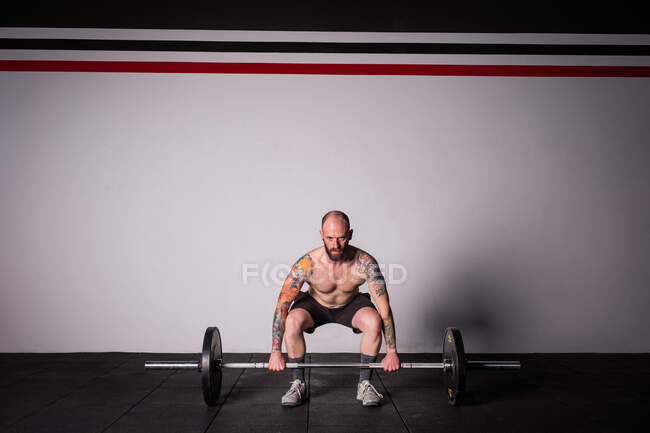 Спортивний молодий сконцентрований хлопець у спортзалі лаяє дзвіночок — стокове фото