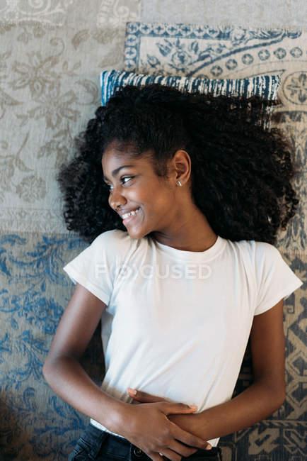 Joven adolescente negro acostado en una alfombra - foto de stock