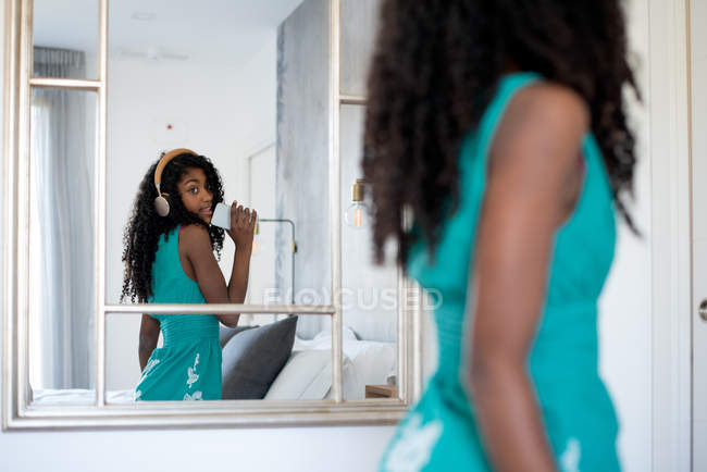 Schwarzes Teenager-Mädchen mit lockigem Haar, lächelnd vor einem Spiegel in die Kamera blickend, Musik über Kopfhörer hörend und auf dem Handy singend — Stockfoto