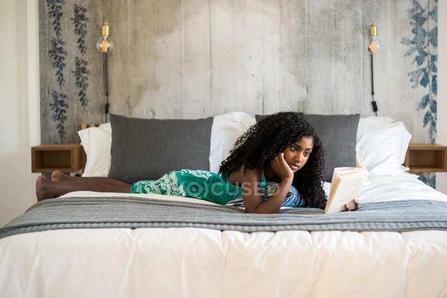 Feliz preto adolescente na cama lendo um livro — Fotografia de Stock