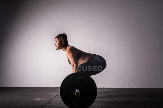 Side view of athletic young concentrated lady in sportswear upping barbell above head in gym — Stock Photo