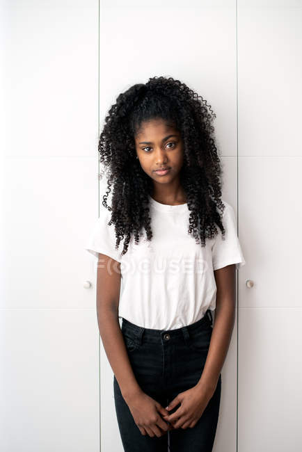 Portrait of young black teenage girl looking into camera in a white background — Stock Photo