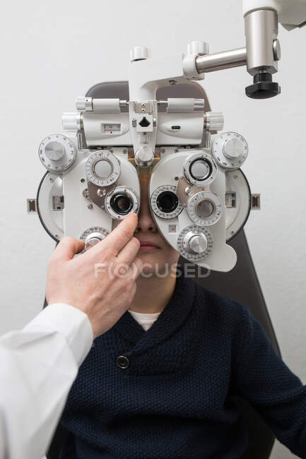 Optician testing a boy's eyes with optometry devices — Stock Photo