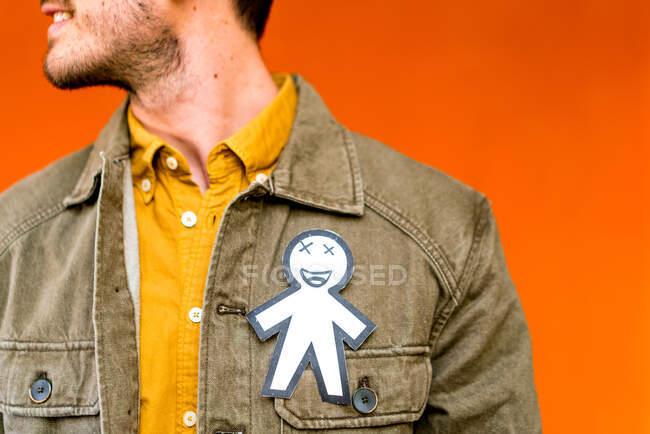 Щасливий хлопець з паперовим силуетом на квітневий день дурень на джинсовому піджаку на оранжевому тлі — стокове фото