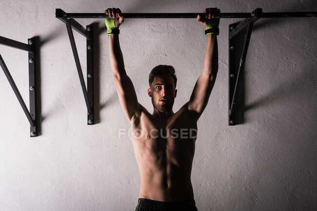 Athletic young shirtless guy hanging on bar near wall in gym — Stock Photo