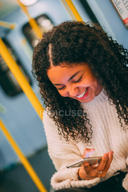 Happy attractive young African American lady with curly hair browsing on mobile phone in public service vehicle — Stock Photo