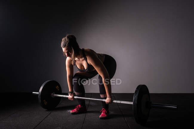 Вид сбоку на атлетичную молодую концентрированную леди в спортивной одежде, поднимающую штангу над головой в спортзале — стоковое фото